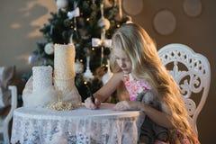 La muchacha cerca de un árbol de navidad con un conejo preferido del juguete escribe una letra a Papá Noel, cajas, la Navidad, Añ Imagen de archivo