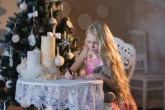 La muchacha cerca de un árbol de navidad con un conejo preferido del juguete escribe una letra a Papá Noel, cajas, la Navidad, Añ Fotografía de archivo