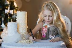La muchacha cerca de un árbol de navidad con un conejo preferido del juguete escribe una letra a Papá Noel, cajas, la Navidad, Añ Fotografía de archivo libre de regalías