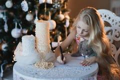 La muchacha cerca de un árbol de navidad con un conejo preferido del juguete escribe una letra a Papá Noel, cajas, la Navidad, Añ Imágenes de archivo libres de regalías