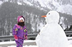 La muchacha cerca de un muñeco de nieve grande fotografía de archivo