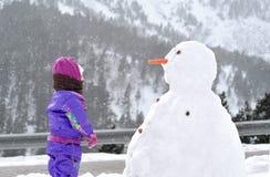 La muchacha cerca de un muñeco de nieve grande foto de archivo