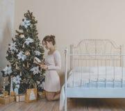 La muchacha cerca del árbol de navidad con los regalos Imágenes de archivo libres de regalías