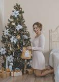 La muchacha cerca del árbol de navidad con los regalos Fotografía de archivo libre de regalías