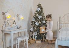 La muchacha cerca del árbol de navidad con los regalos Fotografía de archivo