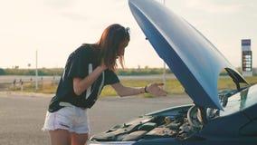 La muchacha cerca del coche quebrado en el camino est? invitando al tel?fono m?vil almacen de video