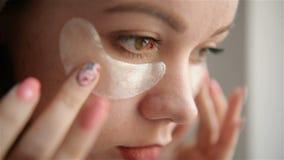 La muchacha cerca del espejo conduce tratamientos de la belleza en la cara La muchacha pone remiendos en el ?rea debajo de los oj almacen de video
