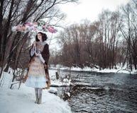 La muchacha cerca del río con el paraguas floral Foto de archivo