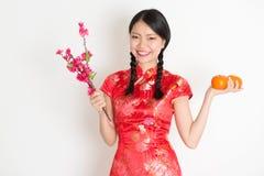 La muchacha china asiática que sostiene la naranja de la mandarina y el ciruelo florecen Imágenes de archivo libres de regalías