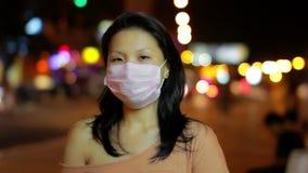 la muchacha china cubre su cara con la máscara en la noche almacen de metraje de vídeo
