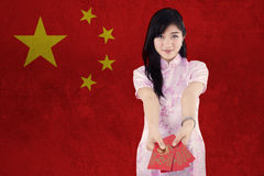 La muchacha china muestra el sobre rojo Fotos de archivo libres de regalías