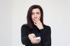 La muchacha chocada cambia el programa sobre la TV Foto de archivo libre de regalías