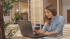 La muchacha cierra el libro en el eje de trabajo almacen de metraje de vídeo