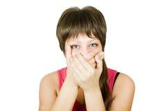 La muchacha cierra su boca con sus manos Fotos de archivo libres de regalías