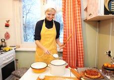 La muchacha cocina la comida Fotos de archivo libres de regalías