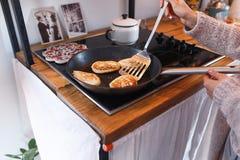 La muchacha cocina las crepes Foto de archivo libre de regalías