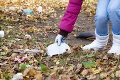 La muchacha coge basura en el parque Foto de archivo