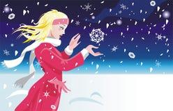 La muchacha coge los copos de nieve Imagen de archivo