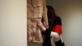 La muchacha coge la ropa para el evento almacen de video