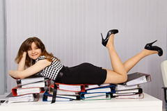 La muchacha coloca comfortablemente en documentos Foto de archivo libre de regalías