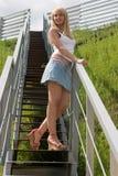 La muchacha coloca en las escaleras. Foto de archivo