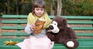 La muchacha come el bollo trenzado con las semillas de amapola en banco cerca de oso de peluche en el patio en parque del otoño metrajes