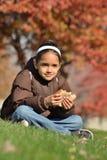 La muchacha come el emparedado en el parque Imagen de archivo