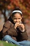 La muchacha come el emparedado en el parque Imágenes de archivo libres de regalías