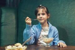 La muchacha come el helado en la tabla Imagenes de archivo