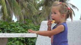 La muchacha come el pan y sentarse en un banco almacen de metraje de vídeo