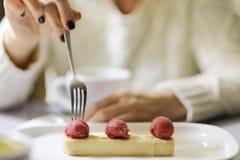 La muchacha come el postre del pastel de queso con la menta en la placa Imagen de archivo libre de regalías