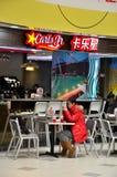 La muchacha come en el JR restaurante Shangai China de Carl de los alimentos de preparación rápida Foto de archivo