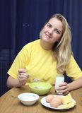 La muchacha come gachas de avena con leche Imagen de archivo