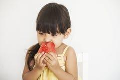 La muchacha come la sandía fotografía de archivo libre de regalías