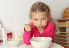 La muchacha come la sopa en casa Imagenes de archivo