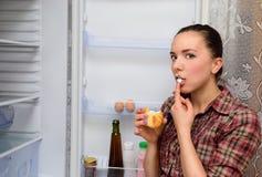 La muchacha come la torta cerca del refrigerador Fotos de archivo libres de regalías