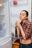 La muchacha come la torta cerca del refrigerador Imagen de archivo