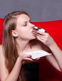 La muchacha come la torta de chocolate Foto de archivo libre de regalías