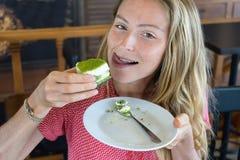 La muchacha come la torta, la muchacha fresca con la torta Fotos de archivo