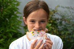 La muchacha come los pasteles Fotos de archivo libres de regalías
