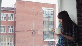 La muchacha come los tallarines inmediatos que se sientan en un alféizar contra un edificio de ladrillo almacen de video