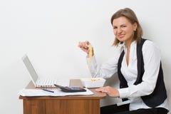 La muchacha come pastas, trabajando detrás del ordenador portátil Imagenes de archivo
