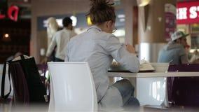 La muchacha come una hora de la almuerzo en un café en una tabla almacen de metraje de vídeo