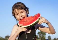 La muchacha come una sandía al aire libre Fotografía de archivo