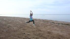 la muchacha comienza a hacer ejercicios de la mañana en la playa en la salida del sol metrajes