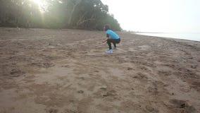 la muchacha comienza a hacer ejercicios de la mañana en la playa en la salida del sol almacen de metraje de vídeo