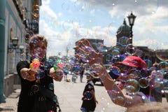 La muchacha comienza para arriba burbujas de jabón en el fondo del ci principal Fotografía de archivo libre de regalías