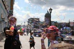 La muchacha comienza para arriba burbujas de jabón en el fondo del ci principal Fotos de archivo libres de regalías