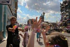 La muchacha comienza para arriba burbujas de jabón en el fondo del ci principal Foto de archivo