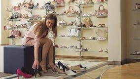 La muchacha compara los zapatos marrones y negros en la tienda almacen de metraje de vídeo